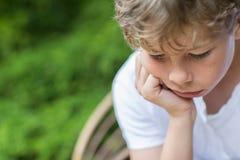 Zamyka Up Nieszczęśliwy chłopiec obsiadanie W krześle Outdoors Obraz Stock
