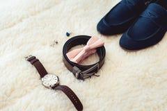 Zamyka up nowożytnego mężczyzna akcesoria Biege bowtie, rzemienni buty, pasek, zegarek, cufflinks, pieniądze i obrączki ślubne, Obrazy Stock
