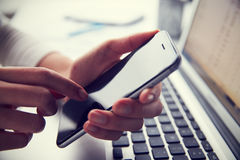 Zamyka Up osoba Przy laptopem Używać telefon komórkowego Fotografia Stock