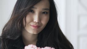 Zamyka up oszałamiająco piękna Azjatycka kobieta wącha goździki zbiory