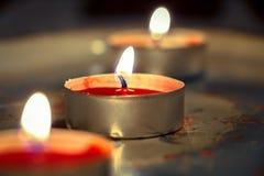 Zamyka up płonące czerwone świeczki na starej tacy Zdjęcia Stock