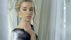 Zamyka up piękna kobieta jest ubranym błyszczących diamentowych kolczyki patrzeje nadokiennego czekanie dla someone