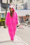 Zamyka up piękna uśmiechnięta młoda kobieta jest ubranym różowego jednorożec kostium, chodzący przy ulicami w mieście Quito Obraz Stock