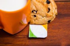 Zamyka up pomarańczowy szkło mleko z czekoladowym ciastkiem piec z stevia, z stevia papierową torbą na drewnianym Zdjęcia Stock