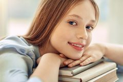 Zamyka up powabnej dziewczyny odpoczynkowy podbródek na książkach Zdjęcia Royalty Free