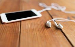 Zamyka up pusty smartphone i słuchawki na drewnie zdjęcie stock
