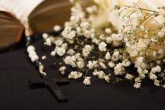 Zamyka up różana koraliki nad świętą biblią z zamazanymi białymi małymi kwiatami, czarny tło Obraz Stock