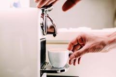 Zamyka up ręka barista browarniana kawa używać kawową maszynę Mężczyzna ` s ręka z filiżanką świeża kawa z pianą Zdjęcia Royalty Free