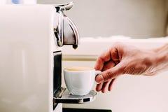 Zamyka up ręka barista robi kawie używać kawową maszynę Mężczyzna ` s ręka z filiżanką świeża kawa z pianą Fotografia Stock