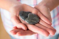 Zamyka Up ręka Trzyma Dwa serce Kształtującego kamienia fotografia stock