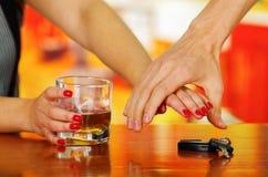 Zamyka up ręka trzyma szkło whisky i męska ręka próbuje unikać kobieta bierze jej samochodowych klucze w barze, Zdjęcia Royalty Free