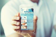 Zamyka up ręka z wiadomości gospodarcze na smartphone obraz royalty free