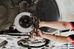 Zamyka up ręka zamienia dyska nowych hamulce podnoszący samochód zdjęcie royalty free