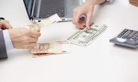 Zamyka up ręki liczy pieniądze przy biurem Obraz Royalty Free