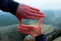 Zamyka up ręki robi ramowemu gestowi Błękitnego mglistego dolinnego bellow skalisty szczyt Dżdżysty wiosna dzień Fotografia Stock