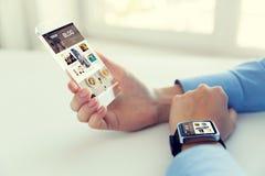 Zamyka up ręki z mądrze zegarkiem i telefonem Obrazy Stock