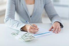 Zamyka up ręki z pieniądze podatku podsadzkową formą Zdjęcie Royalty Free