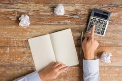 Zamyka up ręki z kalkulatorem i notatnikiem Obraz Stock