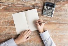 Zamyka up ręki z kalkulatorem i notatnikiem Zdjęcie Stock