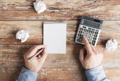 Zamyka up ręki z kalkulatorem i notatnikiem Zdjęcia Royalty Free
