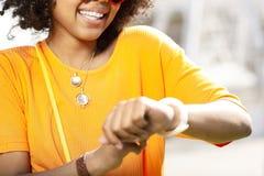 Zamyka up rozochocona kędzierzawa kobieta sprawdza zegarek obrazy stock