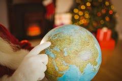 Zamyka up Santa wskazuje jego palec na kuli ziemskiej Fotografia Stock