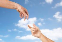 Zamyka up seniora i młodej kobiety ręki nad niebem Zdjęcie Royalty Free
