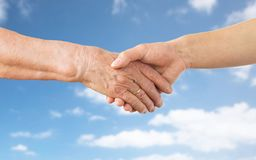 Zamyka up seniora i młodej kobiety ręki nad niebem Obrazy Stock