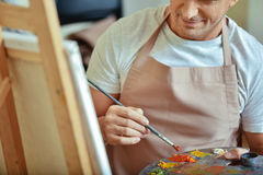 Zamyka up skoncentrowany artysta trzyma paletę i muśnięcie zdjęcia stock