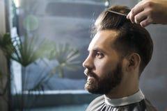 Zamyka up skoncentrowany brown z włosami biznesmen ma jego włosy czeszącego w fryzjera męskiego sklepie obrazy royalty free