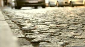 Zamyka up stara brukowiec droga, samochody przechodzi w odległości i Abstrakcjonistyczny rocznik ulicy tło zbiory wideo