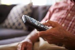 Zamyka Up Starszego mężczyzna obsiadanie Na kanapie Trzyma TV Daleki Fotografia Stock