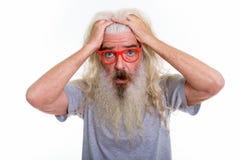 Zamyka up starszy brodaty mężczyzna główkowanie podczas gdy patrzejący szokujących wi obraz stock