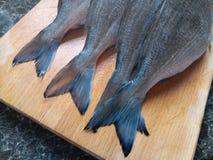 Zamyka up surowej ryba ogony na drewnianej desce obrazy royalty free