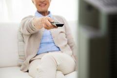 Zamyka up szczęśliwa starsza kobieta ogląda tv w domu Fotografia Stock