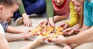 Zamyka up szczęśliwi przyjaciele je pizzę w domu Obraz Stock
