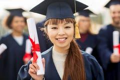 Zamyka up szczęśliwy uczeń lub kawaler z dyplomem obraz stock