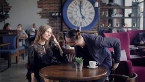 Zamyka up szczupły długowłosy kobiety odprowadzenie przez kawiarni stół z jej męskim przyjacielem Mężczyzna jest trwanie up zdjęcie wideo