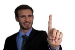 Zamyka up uśmiechniętego biznesmena wzruszający palec wskazujący na niewidzialnym interfejsie Obrazy Royalty Free