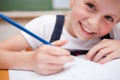 Zamyka up uśmiechnięty uczennicy writing coś obraz royalty free