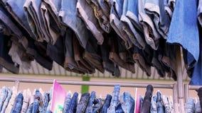 Zamyka up wiele niebiescy dżinsy wiesza na poręczu zbiory wideo