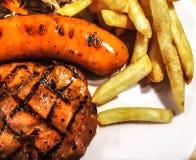 Zamyka up wieprzowin stek Piec na grillu kiełbasy na białym talerzu obrazy stock