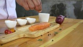 Zamyka up wyśmienity szef kuchni lub gotuje przyprawowego świeżego kawał delikatesy kawałek łosoś ryba z morze solą i gruntującym zdjęcie wideo