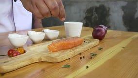 Zamyka up wyśmienity szef kuchni lub gotuje przyprawowego świeżego kawał delikatesy kawałek łosoś ryba z morze solą i gruntującym zbiory wideo