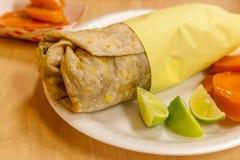 Zamyka up z świeżym burrito z wapno i kiszonymi marchewkami na stronie obraz royalty free