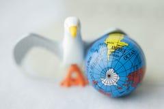 Zamyka up zabawkarski ptak obok ziemskiej kuli ziemskiej przeciw białemu b Zdjęcie Royalty Free