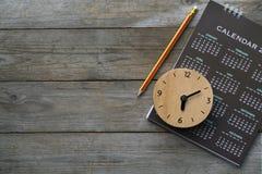 Zamyka up zegar, kalendarz i ołówek na stole, Zdjęcie Stock