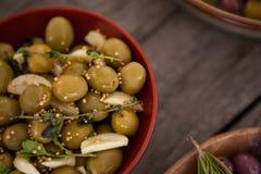 Zamyka up zielone oliwki z pikantnością słuzyć w pucharze Obrazy Royalty Free