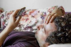 Zamyka up zrelaksowany Kaukaski mężczyzna używa mądrze telefonu lying on the beach na leżance w żywym pokoju w domu Obraz Stock