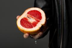 Zamyka w górę fotografii mężczyzna w skórzanej kurtce ten mienia grapefruitowego w jego ręce zdjęcie royalty free